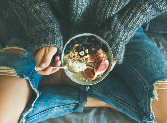 女性は、ブルーベリー、グアバ、シリアルの健康的な朝食ボウルを保持しています。