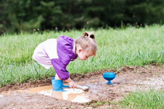 Une jeune fille joue dans la boue.
