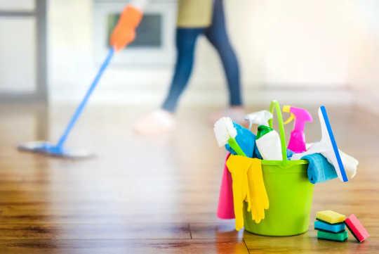 Un seau coloré de produits de nettoyage, avec une femme en arrière-plan.