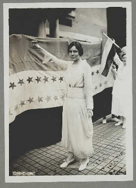 Suffragist Alice Paul dons a white dress and raises a glass shortly after the passage of the 19th Amendment in 1920.