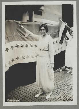 Suffragist Alice Paul trekt een witte jurk aan en heft een glas kort na de passage van het 19e Amendement in 1920.