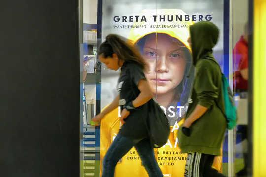 Orang ramai melewati poster untuk buku Greta Thunberg di Itali.