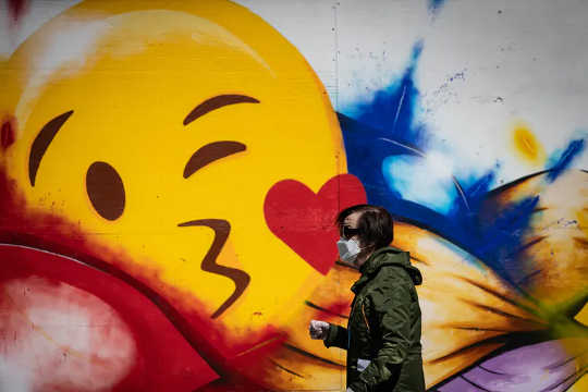 A man wearing a protective face mask and gloves walks past a large emoji face painted on the boarded-up windows of a store on Robson Street, in Vancouver, in May 2020.