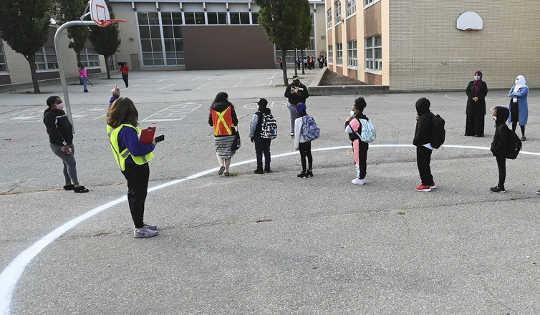 אנשים ממתינים במעגל התרחקות פיזי בחצר בבית הספר הקהילתי Portage Trail בטורונטו ב -15 בספטמבר 2020. (ארבעה צעדים להחלמת מורים מעייפות חמלה ושחיקה)