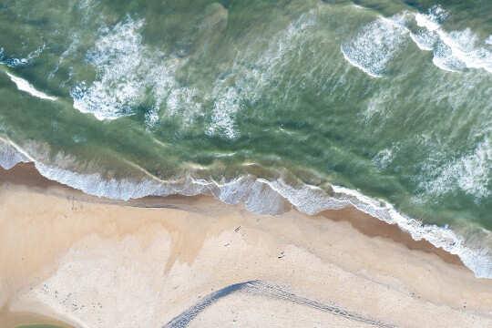 लहरों और समुद्र तट का हवाई दृश्य