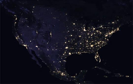 Satellitenbild der USA bei Nacht mit hell beleuchteten Städten.