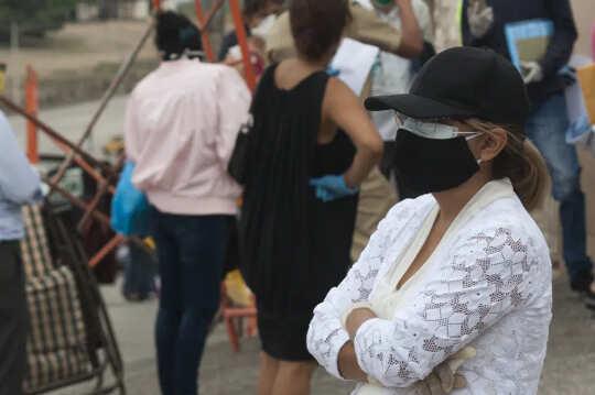 Person, die in einer Menge steht und zwei Masken und einen Hut trägt