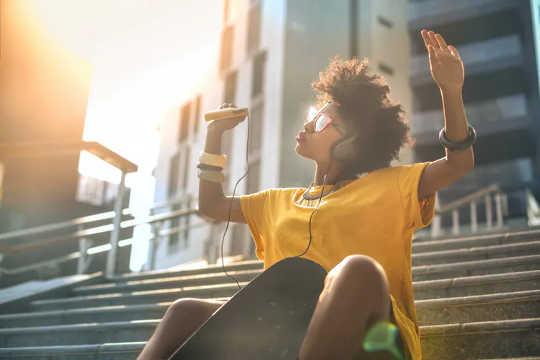Wanita muda yang duduk di tangga, mendengarkan musik dan melambaikan tangannya di udara.
