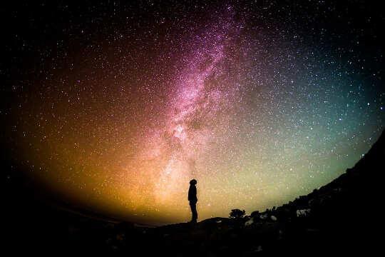 Orang, berdiri dan memandang ke bintang dan Bima Sakti.