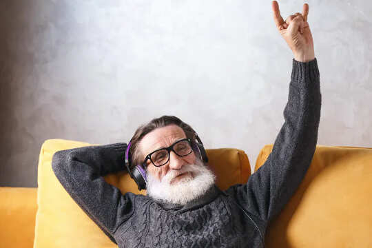 Man with white beard, wearing headsets, sitting on couch and making a Shaka sign with his left hand.