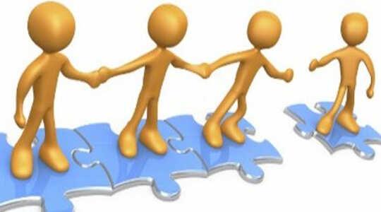 stokfiguren staan op samengevoegde puzzelstukjes, hand in hand en reiken naar een ander figuur op een apart puzzelstuk
