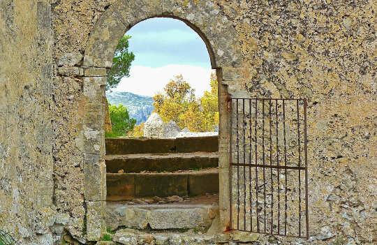Güzel bir doğa manzarasına açılan, taş duvardaki açık bir kapı.