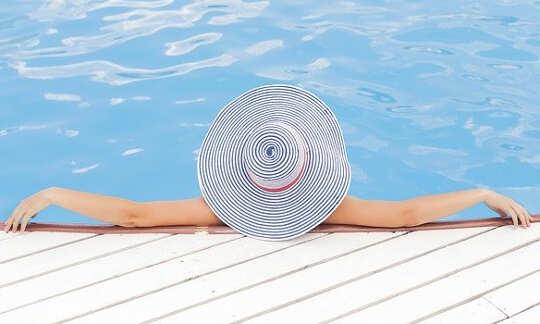 Wanita berbaring di kolam dengan lengan di tepi, mengenakan topi matahari