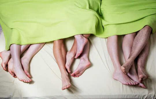 Босые ступни и голени трех пар, лежащих под одним лимонно-зеленым одеялом.