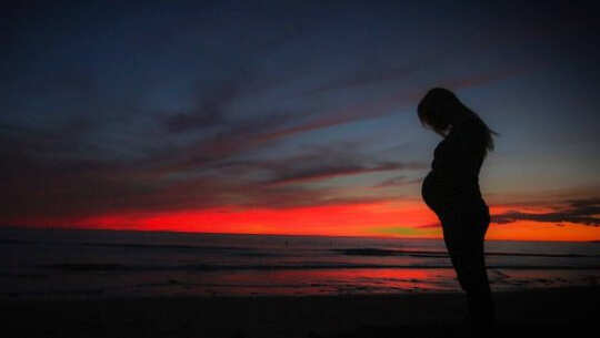 a pregnant woman in silhouette with the sunrise in the background