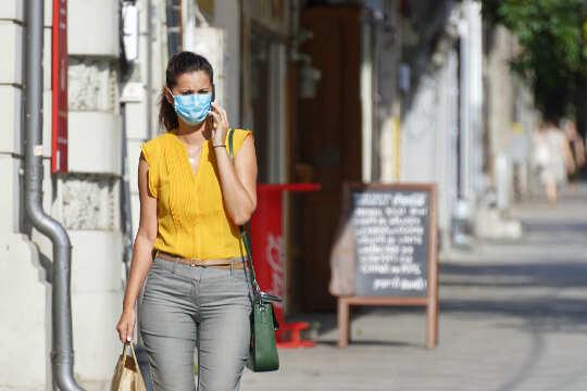 Frau, die die Straße entlang geht, eine Maske trägt und ihr Gesicht berührt