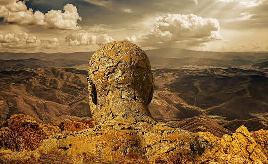 image of the statue of a man made of stones, overlooking a valley