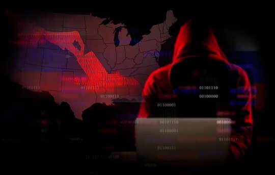 隠れているかのように頭を覆ったコンピューターの影にいる男