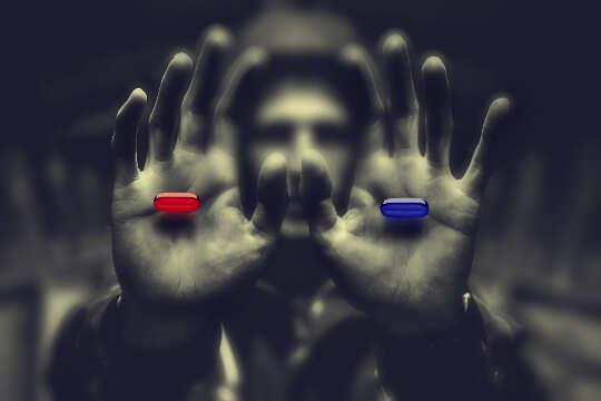 رجل في الظل يمسك حبة حمراء بيد وحبة زرقاء في اليد الأخرى