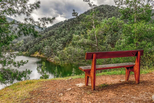 an unoccupied bench overlooking a river in a valley
