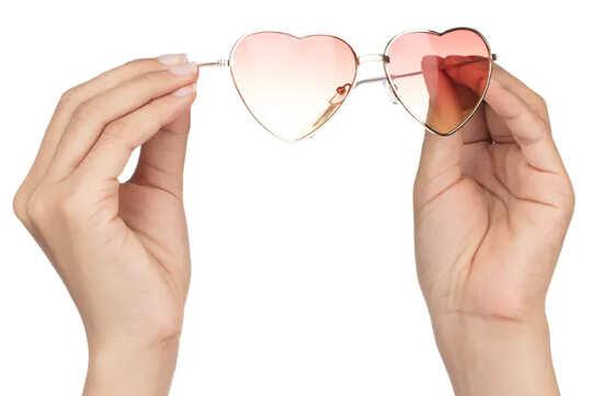 Руки держат розовые очки в форме сердца