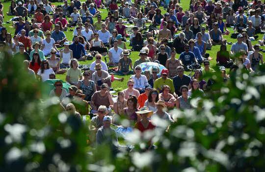 Människor deltar i en massmeditation på gräsmattan på Parliament Hill i Ottawa 2017.