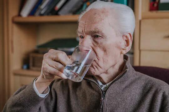 आदमी एक कप से स्पष्ट तरल पी रहा है
