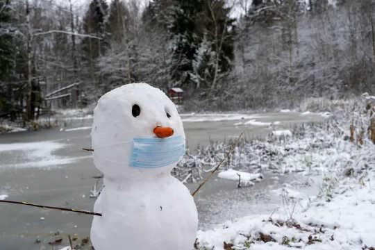 Ein Schneemann mit einer Gesichtsmaske und einer Möhrennase