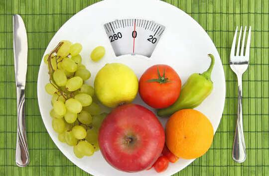 Фрукты и овощи на обеденной тарелке, напоминающей весы для ванной.