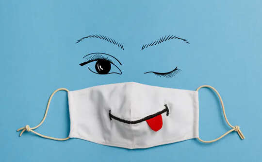 health mask with a smiley face drawn on it with tongue hanging out