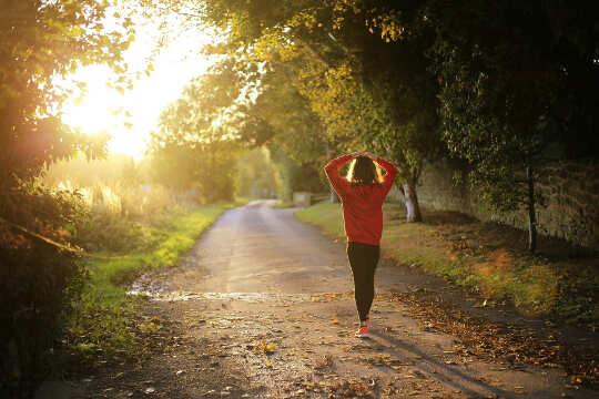 garota caminhando em uma estrada rural em direção a uma luz brilhante à distância