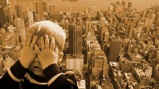 صبي يغطي وجهه كما لو كان خائفًا من منظر المدينة الشاهق خلفه