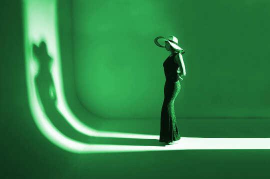 một người mẫu đứng trên đường băng đối mặt với bóng của cô ấy ... tất cả đều màu xanh lá cây