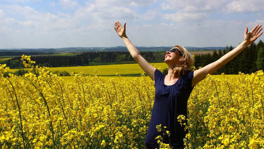 women standing in a field of flowers, smiling with her hands open up to the sky