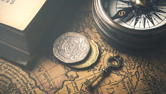 foto av en nyckel, en kompass, mynt, överlagrad på en gammal karta