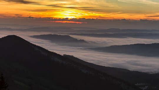 φωτογραφία μιας ανατολής με ομίχλη στην κοιλάδα παρακάτω