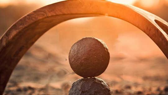 dalawang bola na balansehin sa bawat isa sa ilalim ng arko