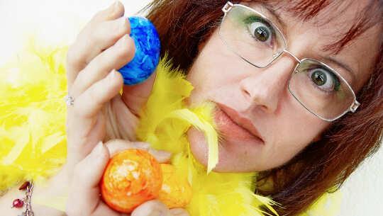 bild av kvinna som håller upp två färgade ägg ... med en förvånad blick i ansiktet
