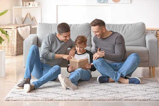 Twee vaders lezen met hun zoon.