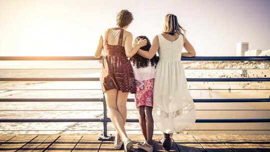امرأتان مع طفل في الوسط يقفان على درابزين ينظران إلى الطبيعة