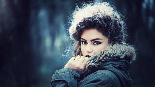 ansikte och axlar av kvinna som bär en vinterparka och tittar på dig