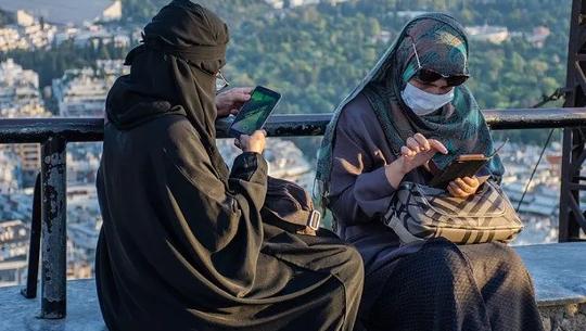 दो मुस्लिम महिलाएं नकाब पहनकर अपने सेलफोन का इस्तेमाल कर रही हैं