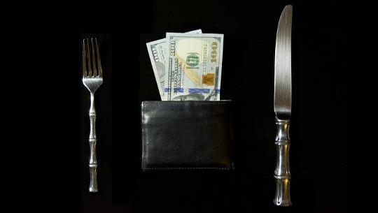 en dukning med kniv och gaffel och en plånbok full med pengar där plattan vanligtvis skulle vara