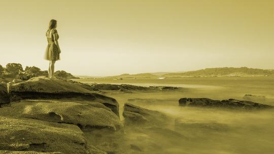 jong meisje kijkt uit over een verlaten monochroom landschap