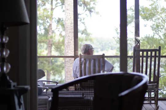 男は森を見渡すバルコニーの椅子に座っています