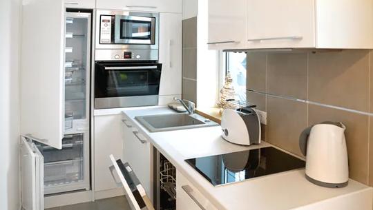 Une petite cuisine avec cuisinière, évier, etc.