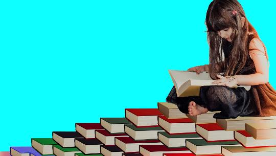 Ung flickasammanträde som omges av massor av bok av olika färger