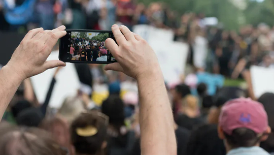 someone taking a picture in a crowd