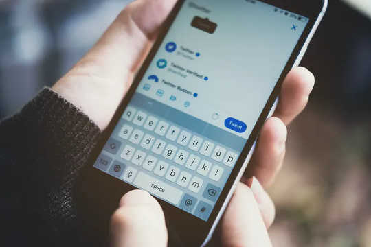 Una mano tiene un telefono con l'app Twitter sullo schermo