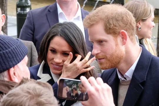 Harry e Meghan vengono fotografati su uno smartphone mentre parlano a una folla